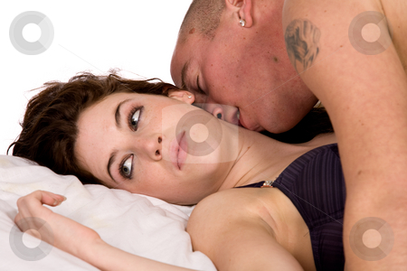 Boyfriend and girlfriend in a passionate kiss stock photo, A young couple being together in bed by Frenk and Danielle Kaufmann