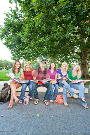 Group of Students - Vertical stock photo, Group of five high school girls and one boy sitting on a bench reading books and smiling. Vertically framed photo. by Orange Line Media