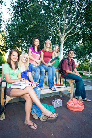 Group of Students - Vertical stock photo, Group of five high school girls and one boy sitting on a bench holding books. Vertically framed photo. by Orange Line Media