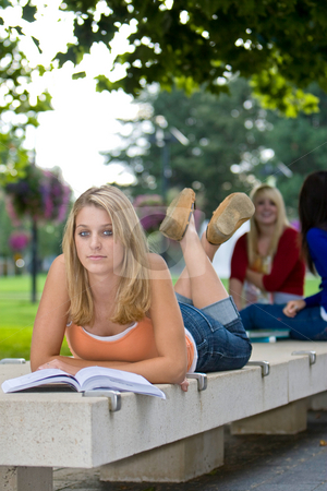 Girl Lying on a Bench - Vertical stock photo, Young female student lying on a bench with other girls on it and reading a book. Vertically framed photo. by Orange Line Media