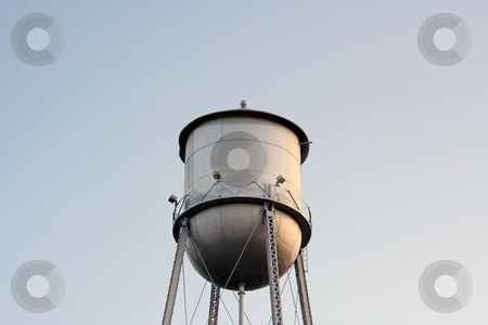 Water Tower stock photo, An old silver water tower lost in the blue sky by Kevin Tietz