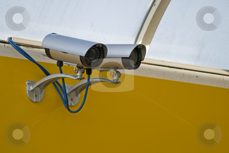 Surveillance camera stock photo, Security camera mounted on a yelow wall by Gert-Jan Kappert
