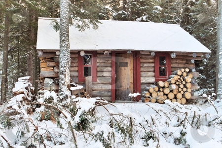 Log cabin in the winter stock photo, A log cabin in the woods during the winter seaso by Tim Markley