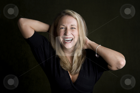 Pretty woman with blue eyes laughing stock photo, Pretty woman with blue eyes and hands behind her head laughing by Scott Griessel