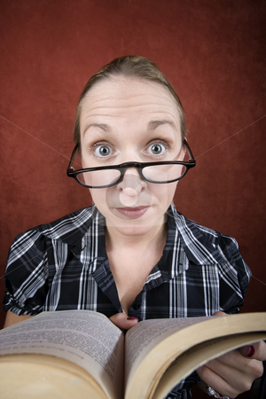 Woman with big eyes reading a book stock photo, Woman with big eyes and glasses reading a book. by Scott Griessel