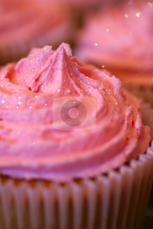 The ultimate fairy cake stock photo, A single cup-cake covered with swirls of pink icing, partially in focus, with similar cup-cakes blurred in the background by Tim Green