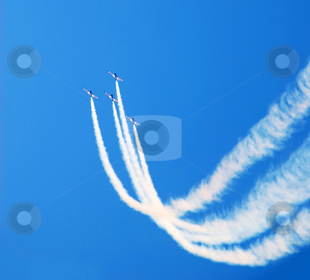 Acrobatic flight stock photo, Planes group in acrobatic flight with smoke trace over blue sky by Julija Sapic