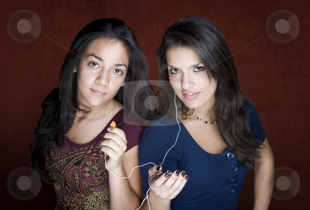 Two young women listening to music stock photo, Two pretty Hispanic women sharing a headset listening to music by Scott Griessel