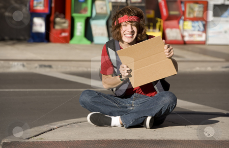 Young Man with Blank Cardboard Sign stock photo, Young Man on Street Corner with Blank Cardboard Sign by Scott Griessel
