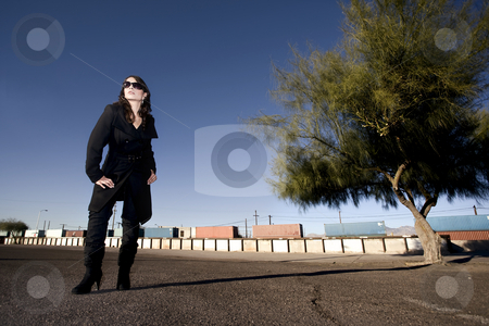 Mysterious Woman in a Trenchcoat stock photo, Mysterious woman in black trenchcoat and sunglasses at train yard by Scott Griessel