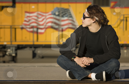 Boy with glasses in front of boxcar stock photo, Teenage boy wearing glasses in front of train by Scott Griessel