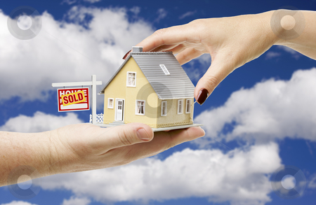 Reaching For A Home with Sold Real Estate Sign stock photo, Reaching For A Home with Sold Real Estate Sign on a Bright Blue Cloudy Sky Background. by Andy Dean