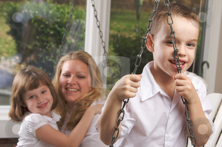 Young Boy Poses with Mom and Sister stock photo, Young Boy Smiles for The Camera as His Mom and Sister Look On by Andy Dean
