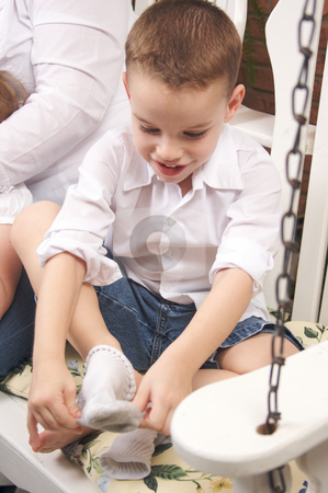 Adorable Young Boy Getting Socks On stock photo, Adorable Young Boy Getting Dressed Putting His Socks On by Andy Dean