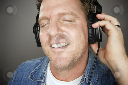 Man Wearing Headphones stock photo, Man Wearing Headphones Enjoying His Music on a Grey Background. by Andy Dean