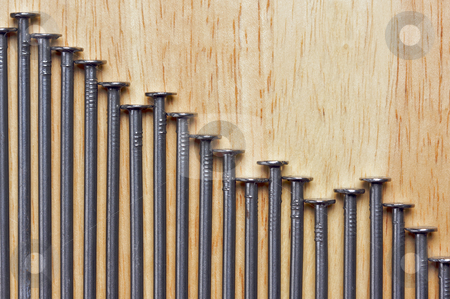 Declining Graph of Nails stock photo, Declining Graph of Nails on a Wood Background. by Andy Dean
