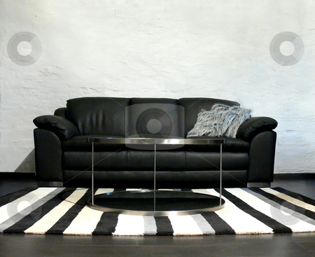 Black Leather Sofa and Striped Rug stock photo, Living room with a black leather sofa, a striped rug and a table by Niklas Ramberg