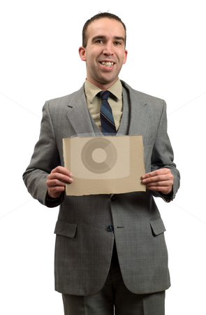 Businessman Holding Cardboard Sign stock photo, A smiling businessman isolated against a white background, holding a small cardboard sign by Richard Nelson
