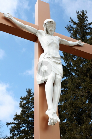 Christ on the Cross stock photo, A statue of Christ on the Cross, with a background of vibrant blue sky and trees by Tom and Beth Pulsipher