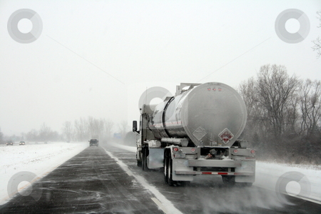 Large Truck on a Winter Highway stock photo, A tanker semi-truck driving along a windswept highway during a winter storm by Tom and Beth Pulsipher