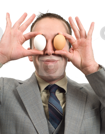 Fun Businessman stock photo, A businessman having fun and using  white and brown eggs to cover his eyes by Richard Nelson