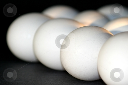 Eggs stock photo, Eggs on a dark background in a group. by Henrik Lehnerer