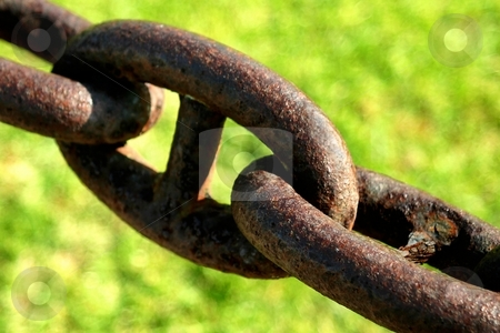Chain stock photo, Old rusty chain with green grass in the background. by Henrik Lehnerer