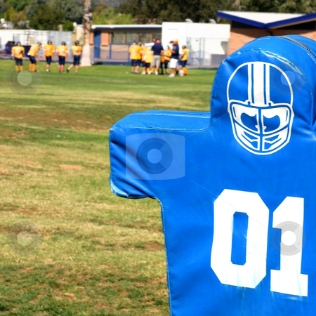 Football Dummy stock photo, Blue tackling dummy for football practice on green grass. by Henrik Lehnerer