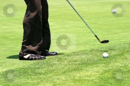 Golf stock photo, Golfer on green lawn ready to play the ball. by Henrik Lehnerer