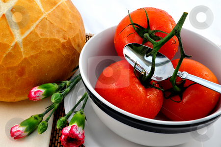 Tomato Soup stock photo, Fresh tomatoes ready for making tomato soup in a white bowl with a loaf of sourdough bread and carnation flowers by Lynn Bendickson