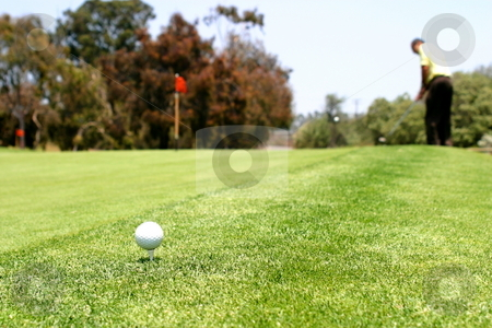 Golf stock photo, Golf ball with a man playing in the background. by Henrik Lehnerer