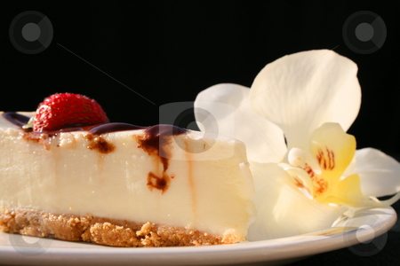 Cheesecake And An Orchid stock photo, Cheesecake and a white orchid on a plate with a black background. by Michael Felix