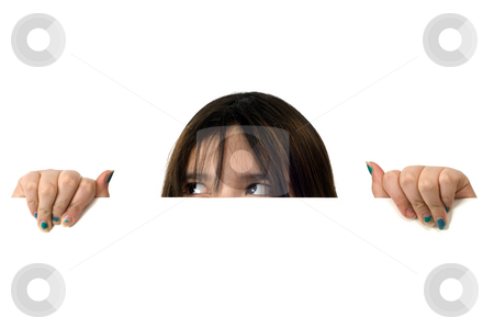 Girl Peeking stock photo, A young girl peeking over a white wall with her eyes looking at an upper corner by Richard Nelson