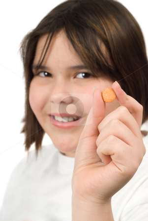 Chewable Vitamin C stock photo, A young girl holding a chewable vitamin C tablet by Richard Nelson