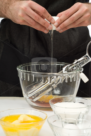 Cracking An Egg stock photo, A male chef cracking an egg into a large glass bowl by Richard Nelson