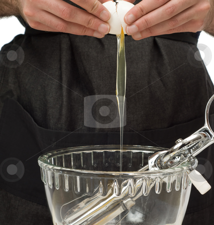 Baking stock photo, A young man preparing an egg to be mixed into some batter by Richard Nelson