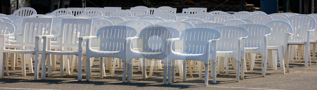 Chairs at a wedding stock photo, White plastic chairs lined up for a wedding by Tim Markley