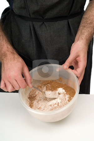 Sifting Ingredients stock photo, A man sifting together ingredients in a bowl by Richard Nelson