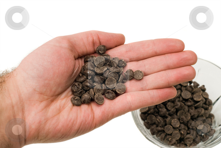 Handful of Chocolate Chips stock photo, Closeup view of a handful of chocolate chips, isolated against a white background by Richard Nelson