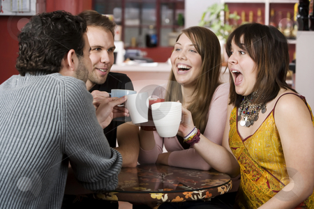 Young Friends Toasting with Coffee Cups stock photo, Young toasting friends with coffee cups in a cafe by Scott Griessel