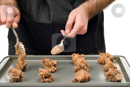 Uncooked Chocolate Chip Cookies stock photo, A man dropping chocolate chip cookies onto a cookie sheet by Richard Nelson
