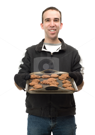 Baker With Cookies stock photo, A young baker holding a sheet of chocolate chip cookies, isolated against a white background by Richard Nelson