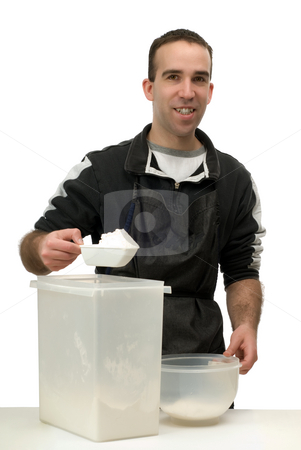 Man Measuring Flour stock photo, Man measuring some flour for his baking, isolated against a white background by Richard Nelson