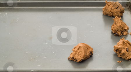 Uncooked Chocolate Chip Cookies stock photo, An old baking pan with chocolate chip cookies getting prepared to be baked by Richard Nelson