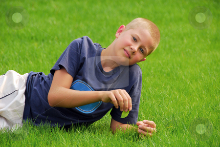 Young boy is resting on the grass stock photo, Young boy is resting on the grass in the garden by Joanna Szycik