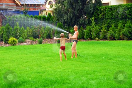 Boys play on the grass stock photo, Two boys play on the grass near house by Joanna Szycik