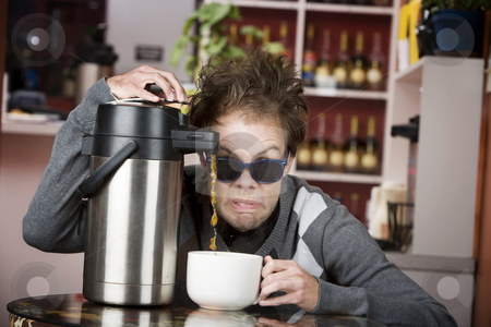 Coffee Crazed Young Man stock photo, Young man crazily pouring coffee from a thermos in a cafe by Scott Griessel