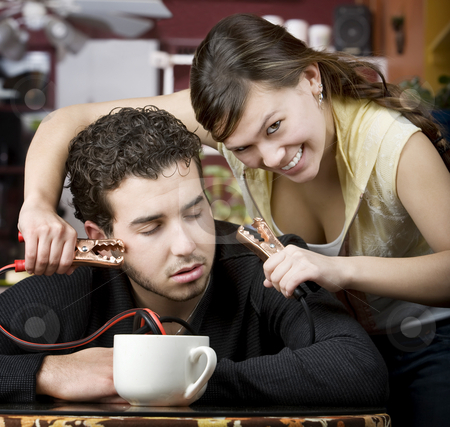 Coffee Jolt stock photo, Young woman holding jumper cables coming out of coffee mug to man's head by Scott Griessel