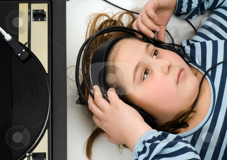 Girl Listening To Music stock photo, Girl lying on the floor listening to music from an old record player by Richard Nelson