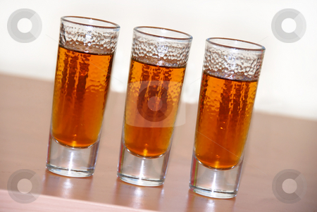 Alcohol drink stock photo, Three small glasses of brown alcohol drink closeup by Julija Sapic